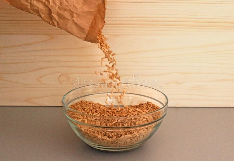 Pouring oats from a paper bag into a bowl. Pouring oats from a brown paper bag into a glass bowl in a kitchen with a wooden background royalty free stock photo