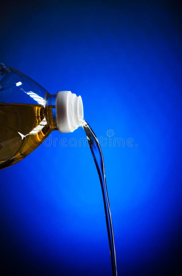 Pouring oil. From bottle, blue background stock photo