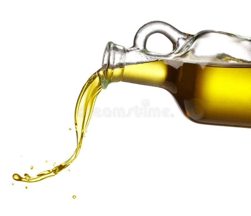 Pouring olive oil. From glass bottle against white background royalty free stock photography