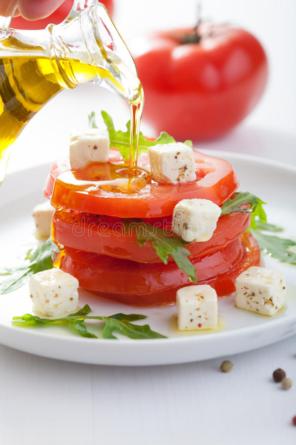 Pouring olive oil over salad with beef tomatoes and feta. Pouring olive oil over fresh salad with beef tomatoes and feta royalty free stock images