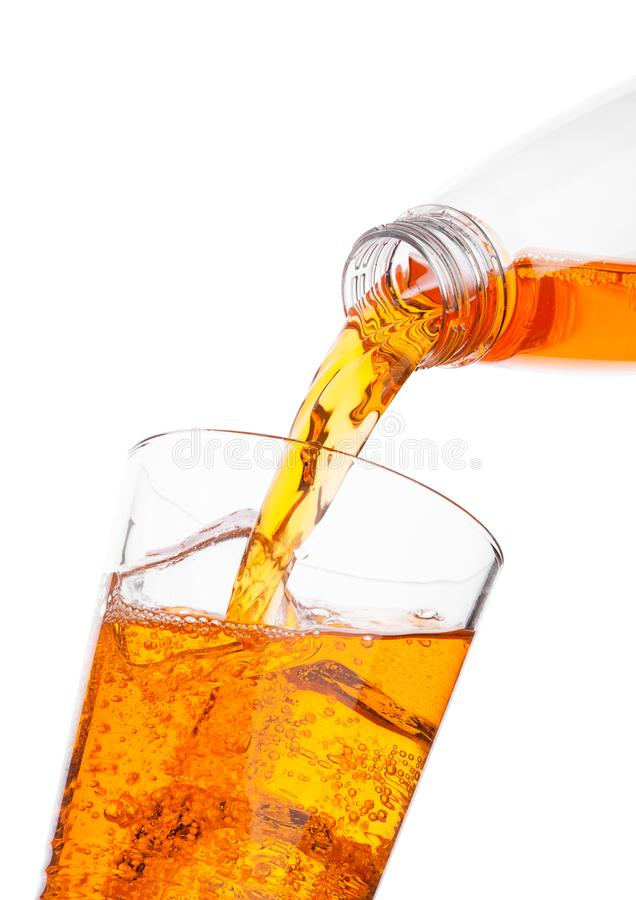 Pouring orange energy drink from bottle to glass. Pouring orange energy soda drink from bottle to glass on white background royalty free stock image
