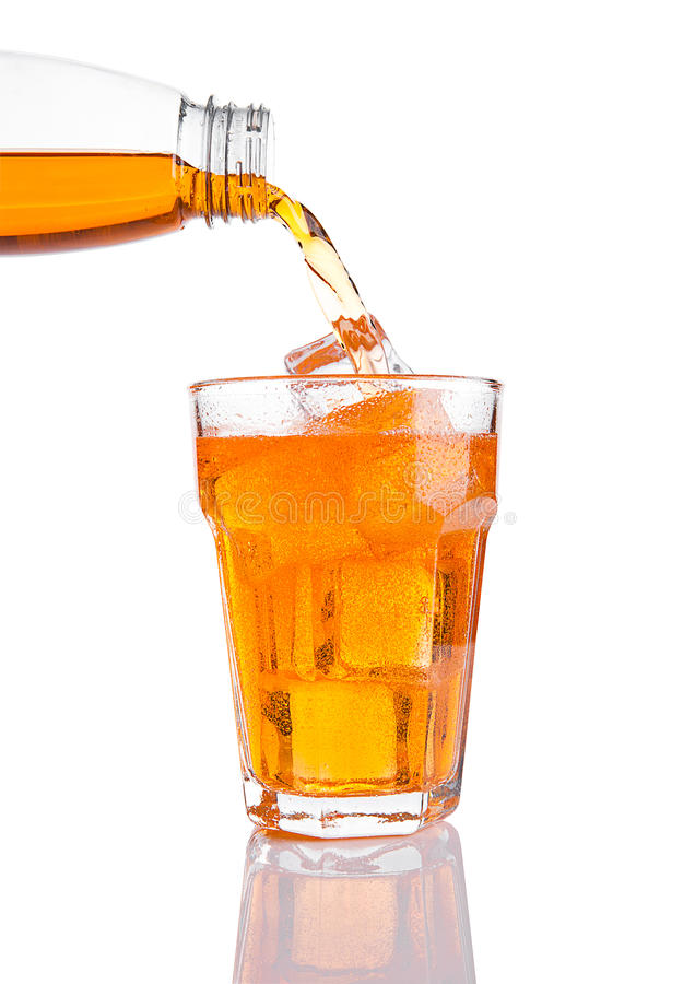 Pouring orange energy soda drink in glass with ice. On white background royalty free stock photography
