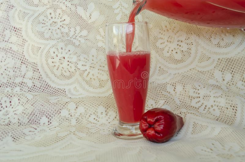 Pouring Otaheite Apple Juice. Otaheite apple juice pouring from the spout of a jug into drinking glass sitting on a white lacey tablecloth. Beside the glass is a stock photography