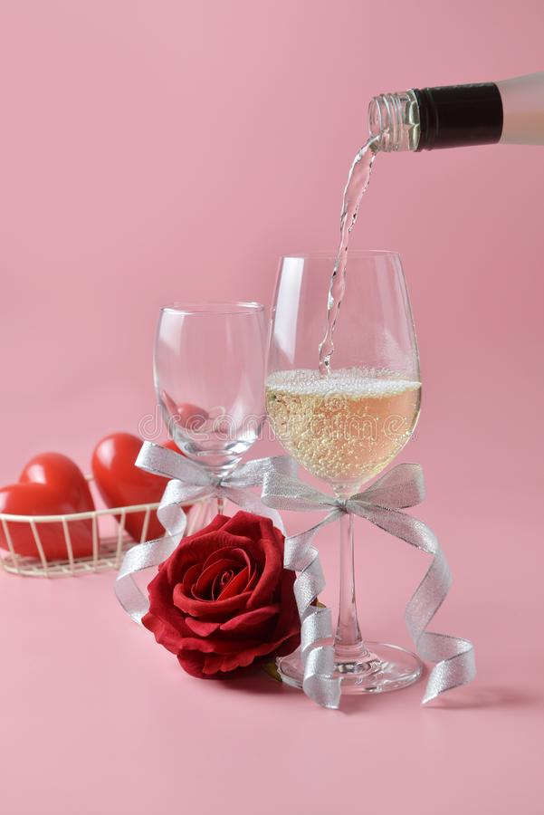 Pouring out of white wine from bottle to glass, with rose at the bottom on pink background. Concept of Valentine`s Day royalty free stock photography