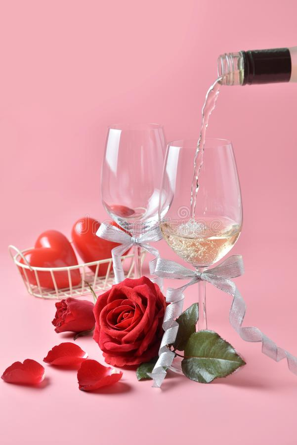 Pouring out of white wine from bottle to glass, with rose at the bottom on pink background. Concept of Valentine`s Day, pop art c stock images