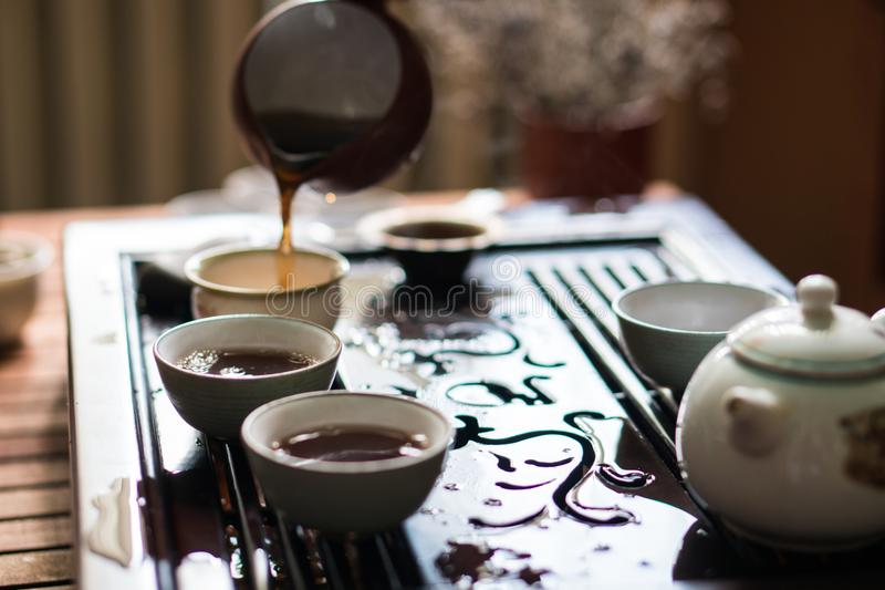 Pouring of Puer Tea from Gaiwan at Traditional Chinese Tea Ceremony. Set of Equipment for Drinking Tea. Man Pouring Puer Tea from Gaiwan Teapot at Traditional royalty free stock photography