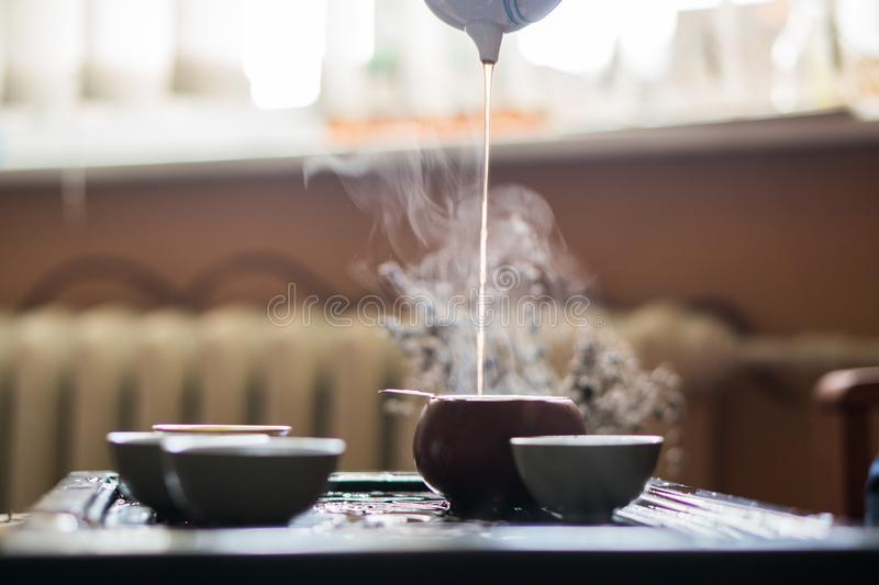 Pouring of Puer Tea from Teapot at Traditional Chinese Tea Ceremony. Set of Equipment for Drinking Tea. Man Pouring Puer Tea from Teapot at Traditional Chinese royalty free stock images