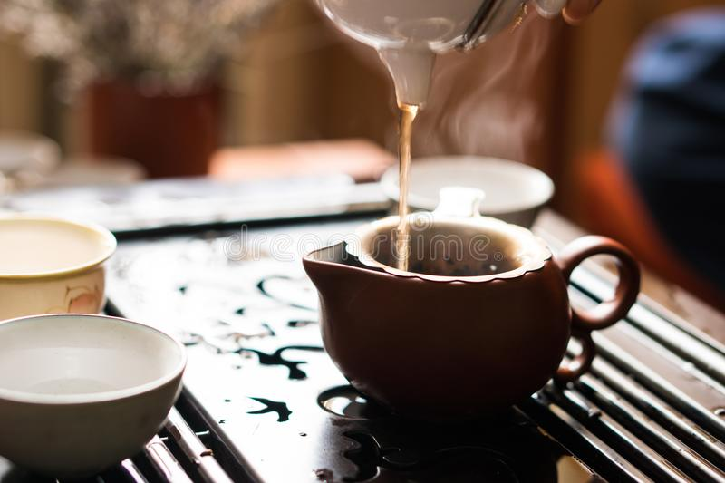 Pouring of Puer Tea from Teapot at Traditional Chinese Tea Ceremony. Set of Equipment for Drinking Tea. Man Pouring Puer Tea from Teapot at Traditional Chinese royalty free stock photography