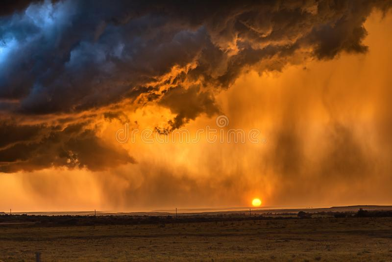Pouring rain at sunset in Tornado Alley. Pouring rain during a lightning storm framed by a low, orange sunset shot in the Great Plains Tornado Alley, Roswell stock images