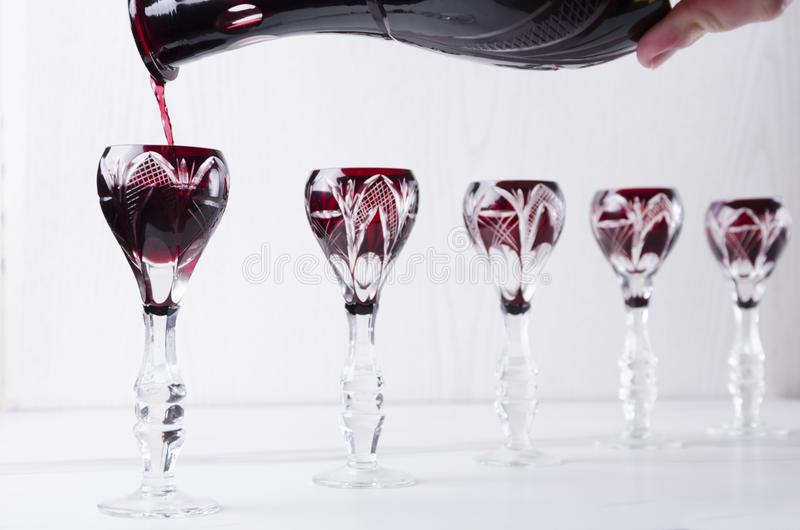 Alcoholic drink tasting.Pouring red liquor into vintage glasses royalty free stock photography