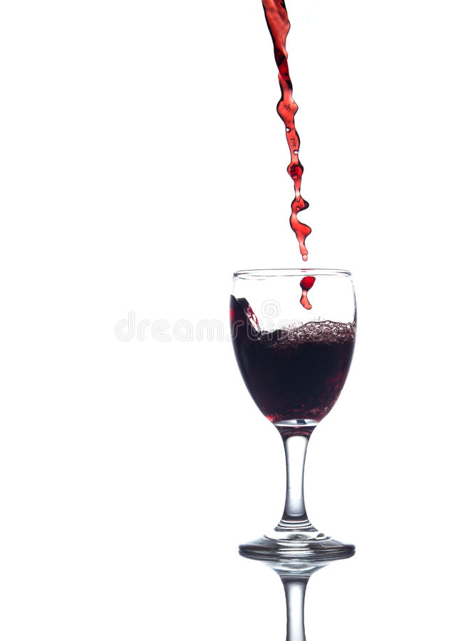 Pouring red water. In to a glass on white background stock images