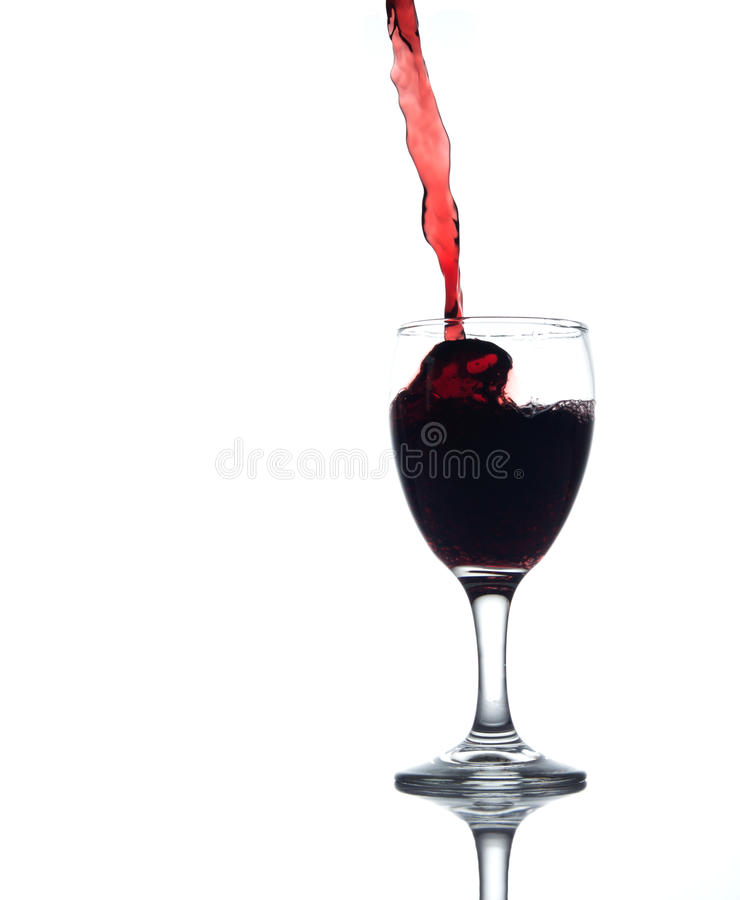 Pouring red water. In to a glass on white background royalty free stock photo