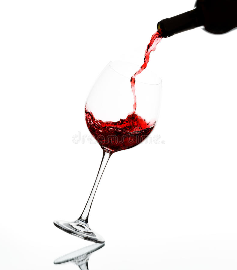 Pouring red wine. Into wine glass on reflective surface stock photos