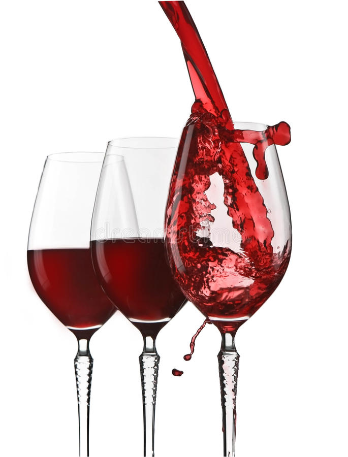 Pouring red wine. In elegant glass on white stock photos