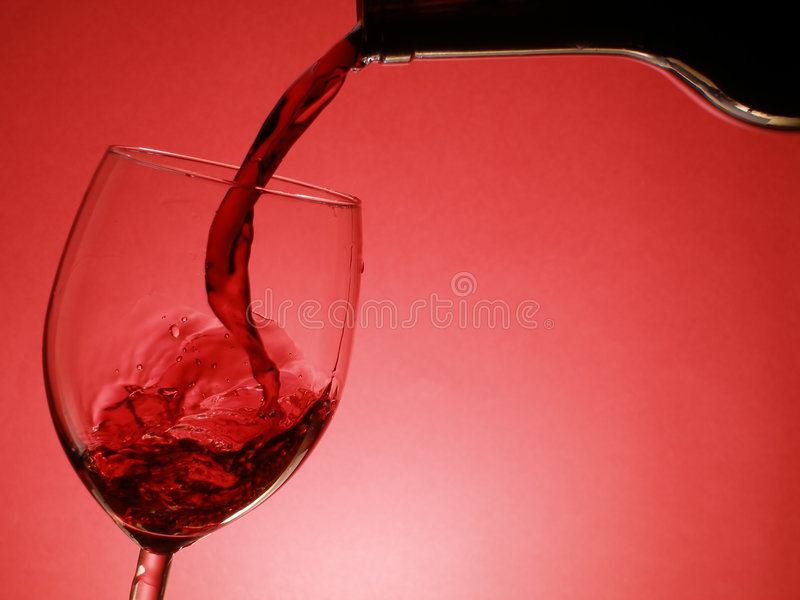 Pouring red wine. Red wine pouring into the glass over red background stock images