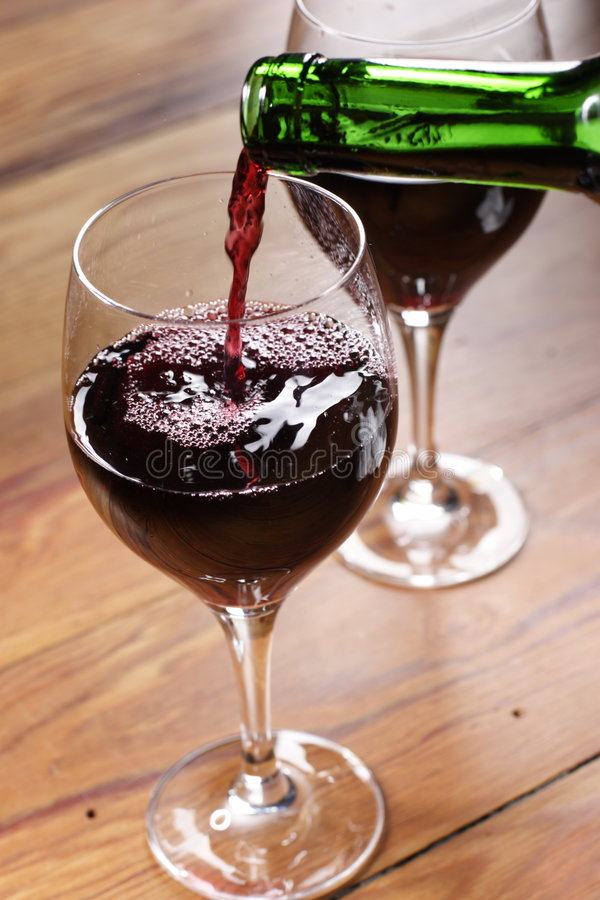 Pouring red wine. Into the glass royalty free stock photos