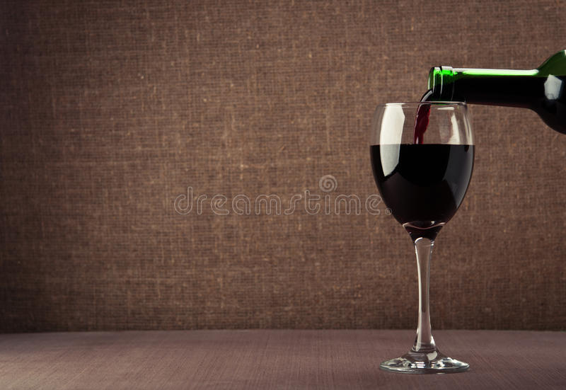 Pouring red wine. On background stock photography