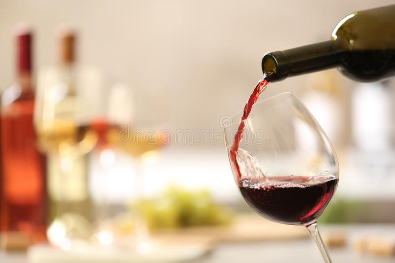 Pouring red wine from bottle into glass on blurred background. Space for text royalty free stock photos