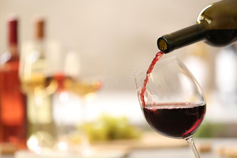 Pouring red wine from bottle into glass on blurred background. Space for text royalty free stock image