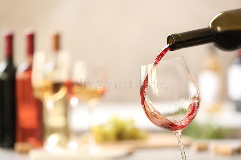 Pouring red wine from bottle into glass on blurred background. Space for text royalty free stock photography