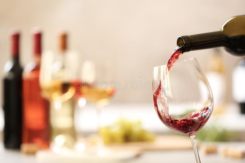 Pouring red wine from bottle into glass on blurred background. Space for text stock photography