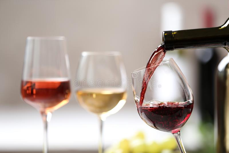 Pouring red wine from bottle into glass on blurred background. Space for text royalty free stock images