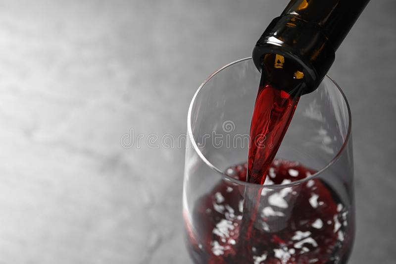 Pouring red wine from bottle into glass on grey background, closeup. Space for text royalty free stock photos