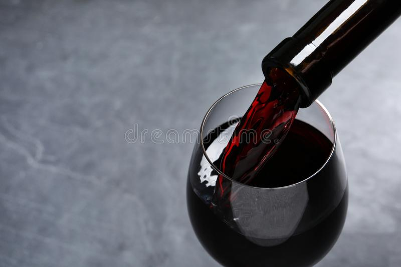 Pouring red wine from bottle into glass on grey background, closeup. Space for text royalty free stock photo