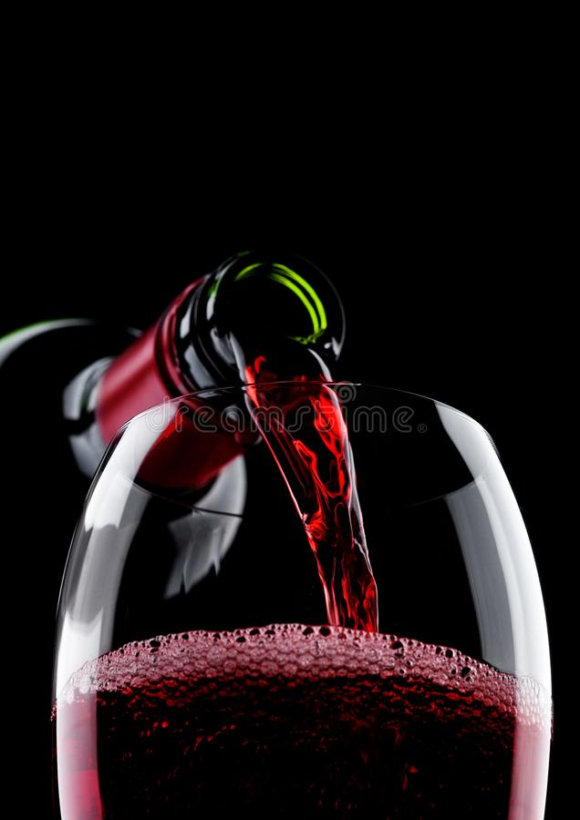 Pouring red wine from bottle to glass on black. Pouring red wine from bottle to glass isolated on black background stock image