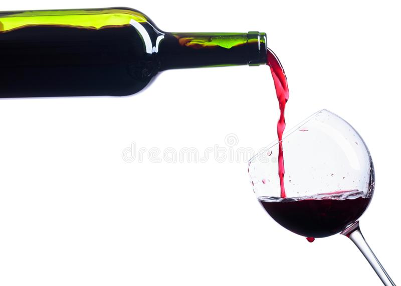 Pouring red wine from bottle to glass isolated on white stock photography