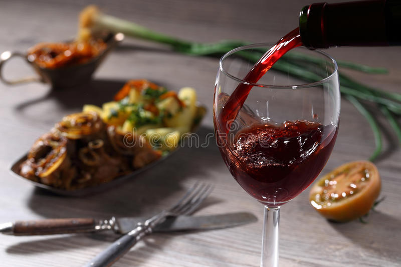 Pouring red wine and food. Background royalty free stock image
