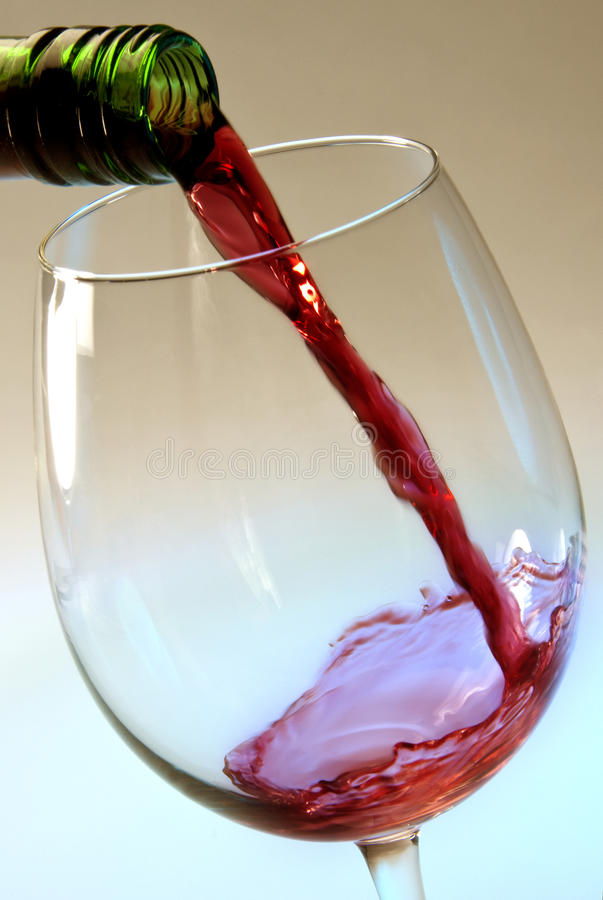 Pouring red wine into a glass. Pouring red wine into a wine glass stock photography