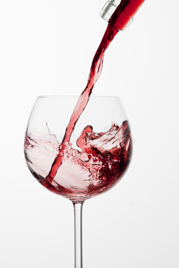 Pouring red wine into glass. Pouring red wine into glass from bottle stock photos