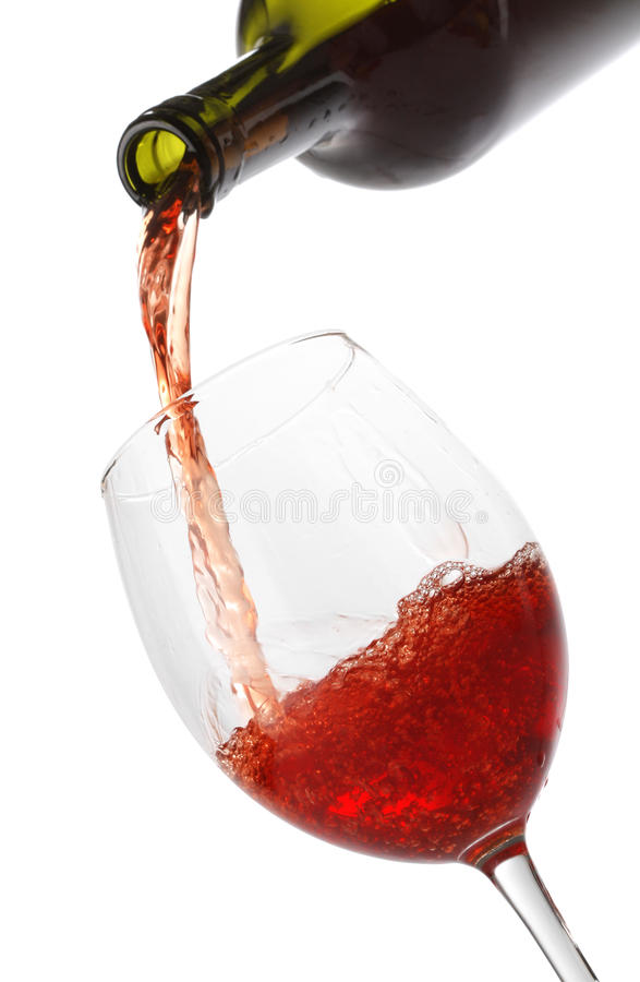Pouring red wine into a glass. Isolated on white royalty free stock photos