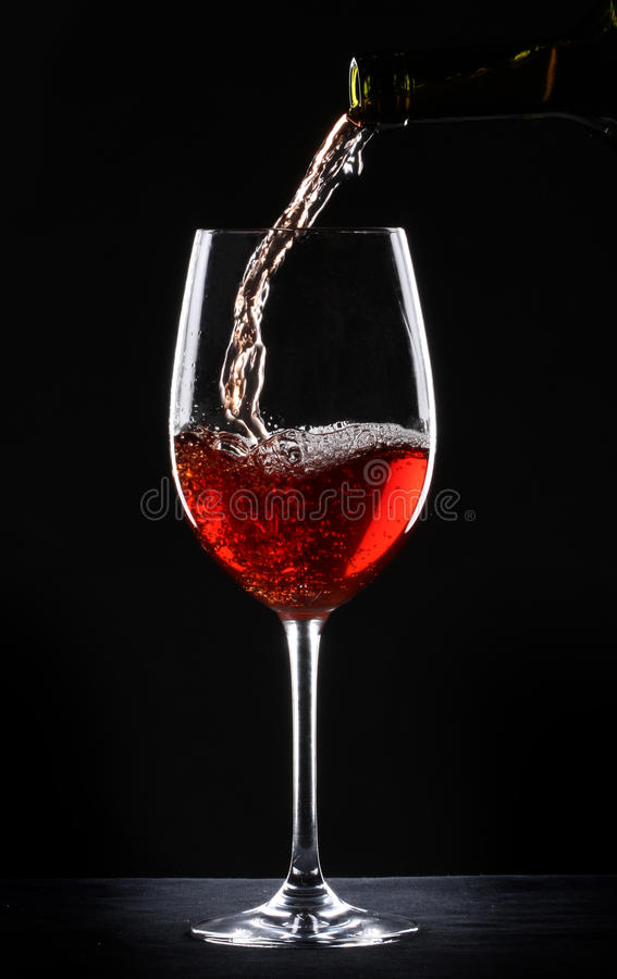 Pouring red wine into a glass. Over black background stock photos