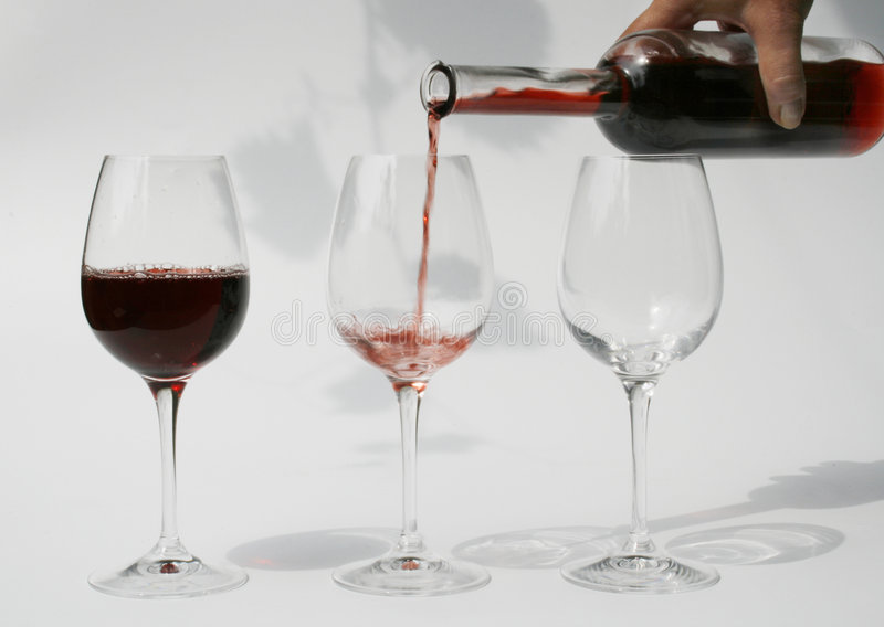 Pouring red wine into glass royalty free stock photo