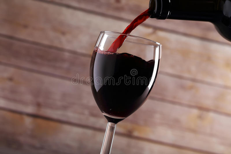 Pouring red wine. Into glass royalty free stock photo