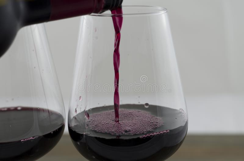 Pouring red wine into the glass. Against. Two wine glasses, one full to the other, is filled with red wine stock photos