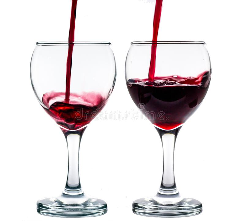 Pouring red wine into the glass against white background. Pouring red wine into the two glasses against white background royalty free stock photos