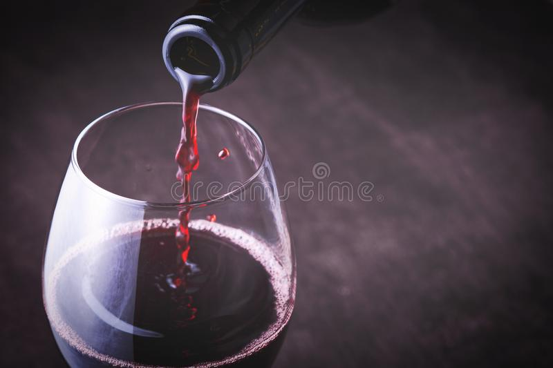 Pouring red wine into the glass. Against wooden background. Bottle royalty free stock photos