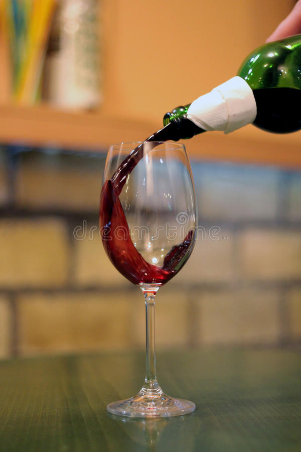 Pouring red wine in glass at bar royalty free stock photography