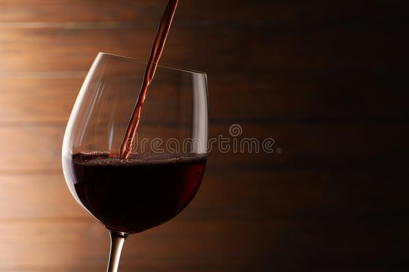 Pouring red wine into glass on blurred background. Space for text stock images