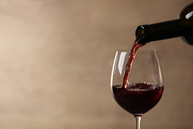 Pouring red wine into glass from bottle against blurred beige background, closeup. Space for text royalty free stock photo