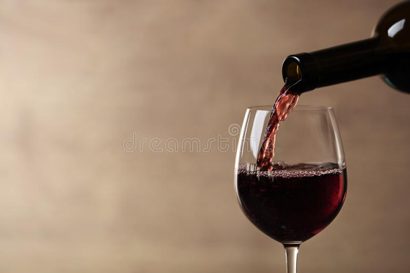 Pouring red wine into glass from bottle against blurred beige background, closeup. Space for text royalty free stock photos
