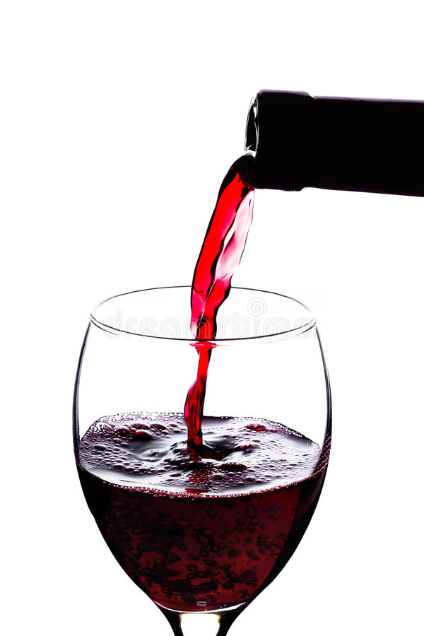 Pouring red wine. On a glass over a white background royalty free stock photo
