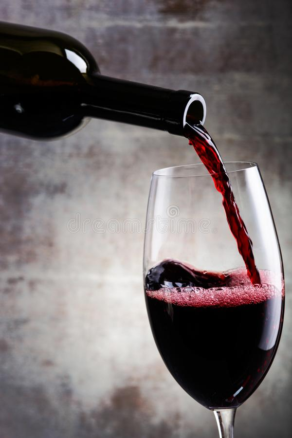 Pouring red wine into the glass. Against wooden background. Bottle royalty free stock photo
