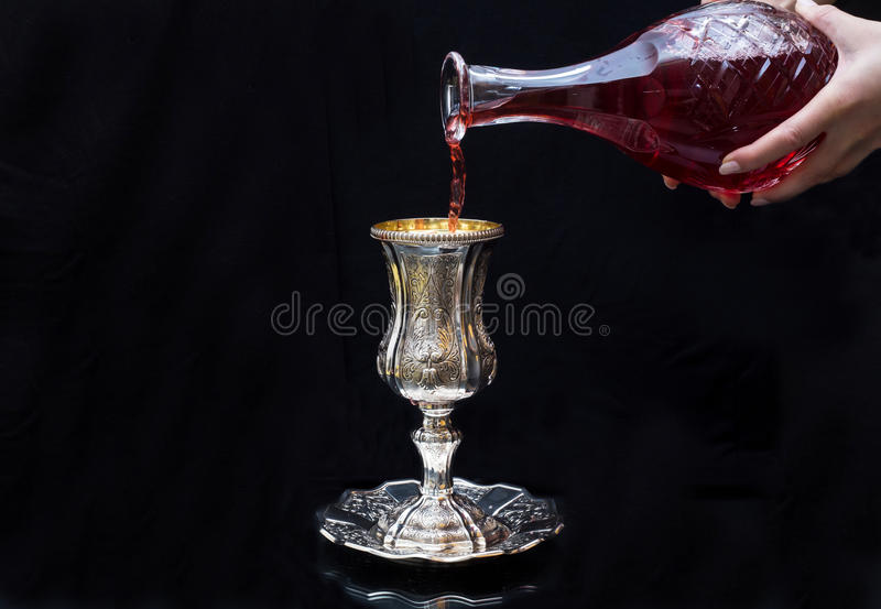 Pouring red wine into a glass Silver royalty free stock photography