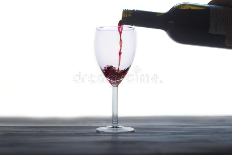 Pouring red wine into a glass royalty free stock photos