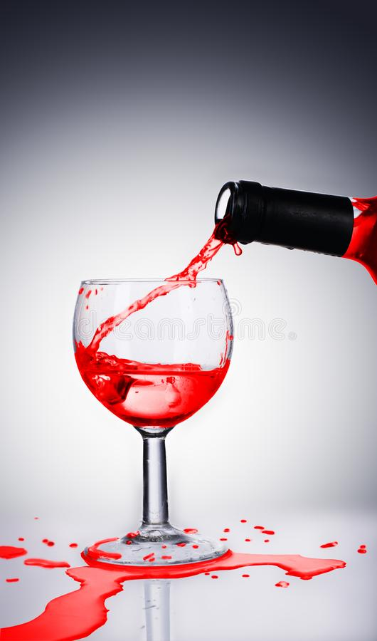 Pouring red wine. Into the goblet royalty free stock photo