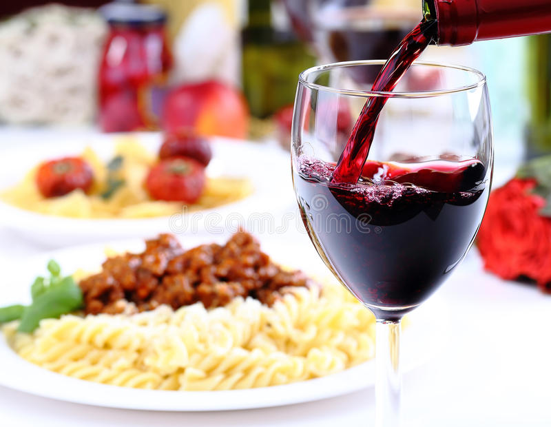 Pouring red wine and pasta. Pouring red wine and food background royalty free stock photo
